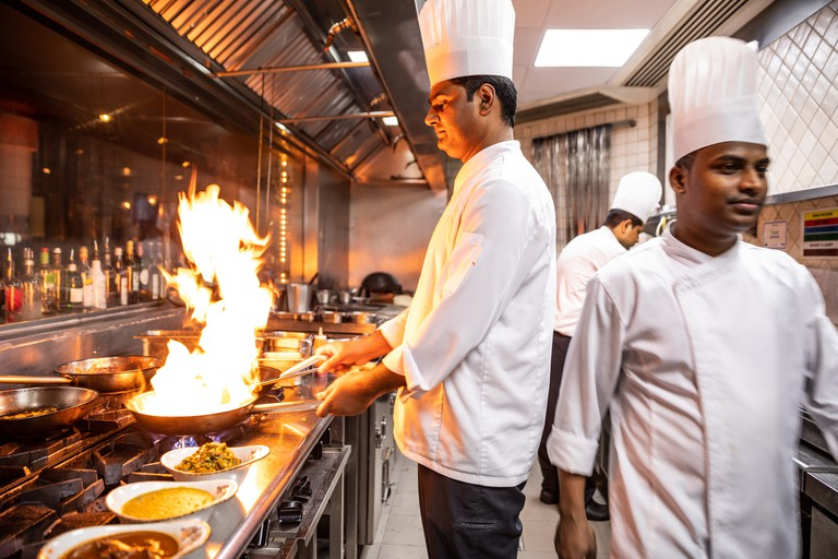 Chefs cooking in a professional kitchen of a gourmet restaurant, Dubai