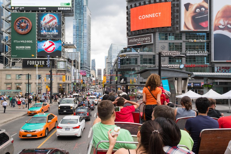 Downtown Toronto -Dundas Square - tourists on hop on hop off bus tour at Yonge-Dundas Square, Toronto, Canada