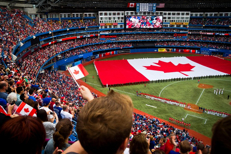 The crowd watches a Canadian flag being rolled out while the national anthems are sung on Canada Day at the Rogers Centre in Toronto, Canada.