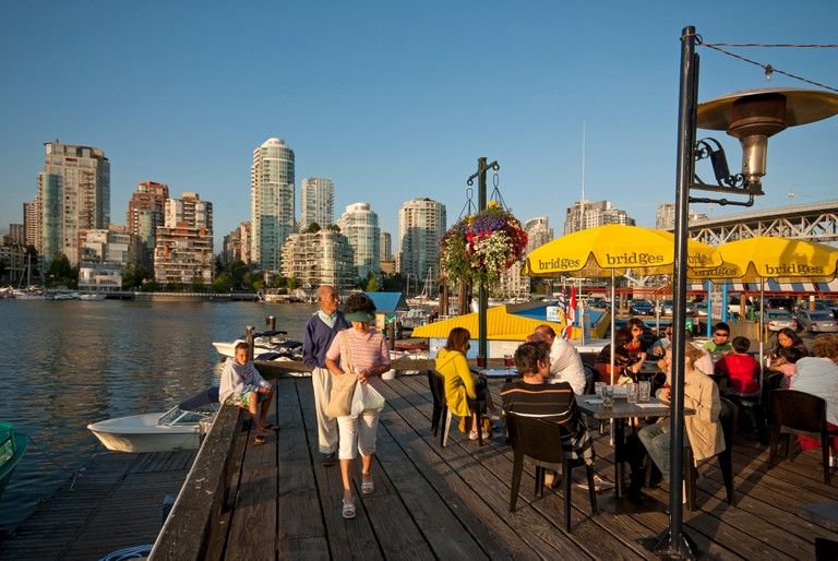 People dining on the terrace of the Bridges Restaurant, Granville Island, Vancouver.