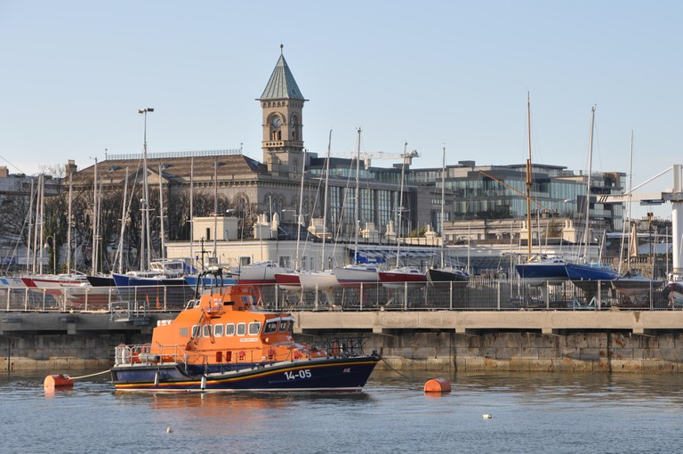 Lifeboat moored in Harbour in Dun Laoghaire with the Town Hall behind