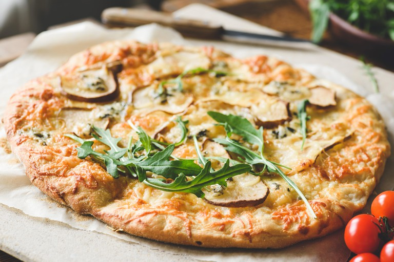 Homemade four cheese pizza with pear and fresh arugula, ruccola. Closeup view, selective focus