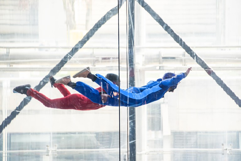 Skydivers in indoor wind tunnel