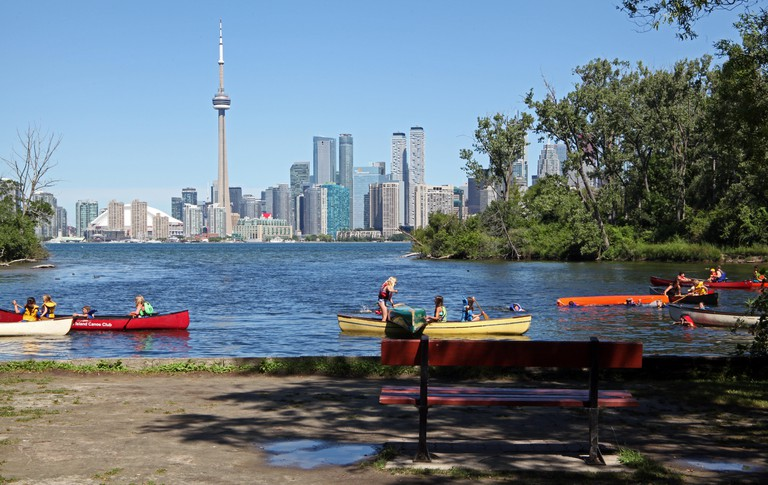 Children in canoes on Toronto Islands with the Toronto city skyline in the background.