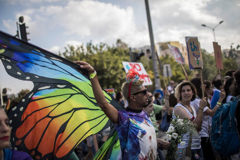 A man, wearing rainbow-themed wings, takes part in the annual Gay Pride Parade in Jerusalem