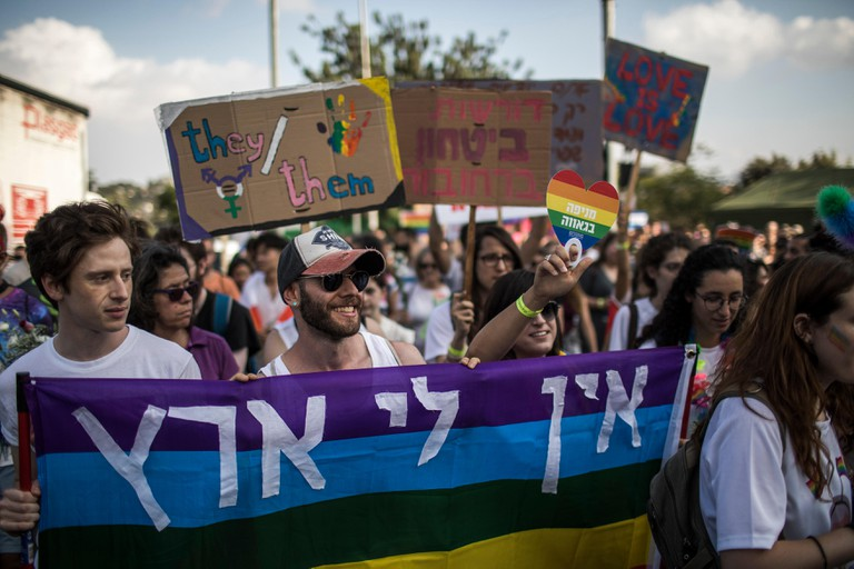 People hold placards and rainbow flags during the annual Gay Pride Parade in Jerusalem