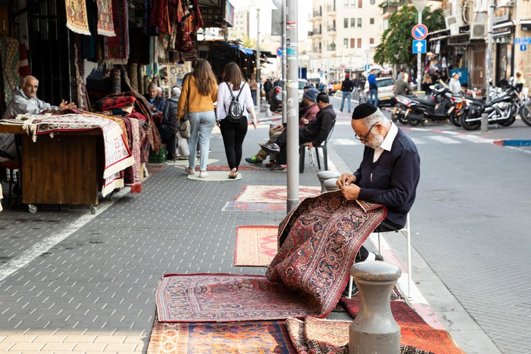 A carpet seller repairing a rug on the street in front of his shop in famous flea market