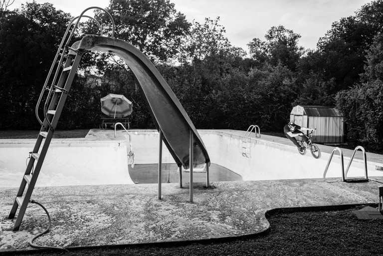 DEAN SCHRALP peg grinds an abandoned pool in Austin, TX.