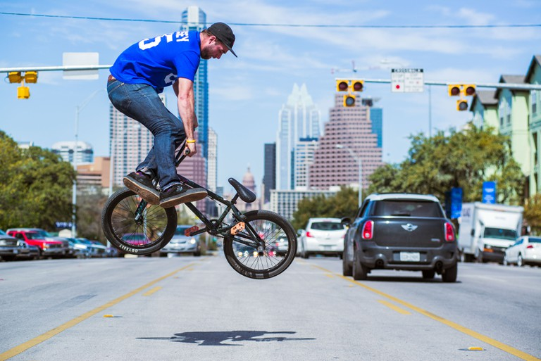 AARON ROSS whips in traffic in Austin's SOCO district to an Austin skyline.