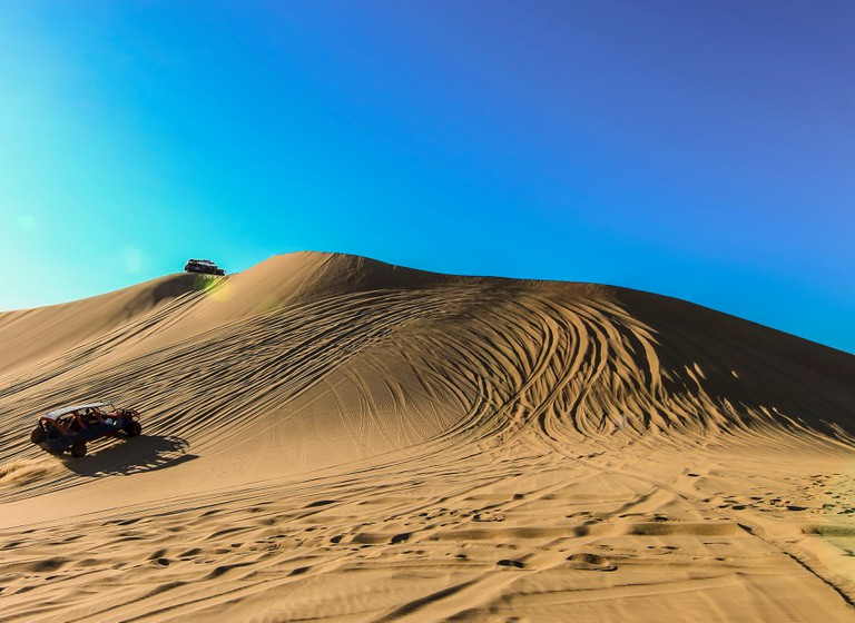 Sand dunes and buggies against clear blue sky at Huacachina, Peru