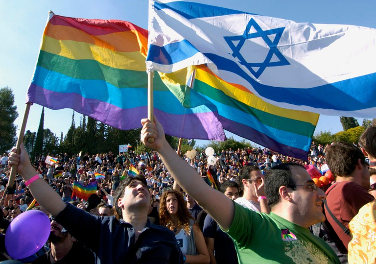 Israelis wave an Israeli flag and a rainbow flag at a controversial gay pride rally in Jerusalem