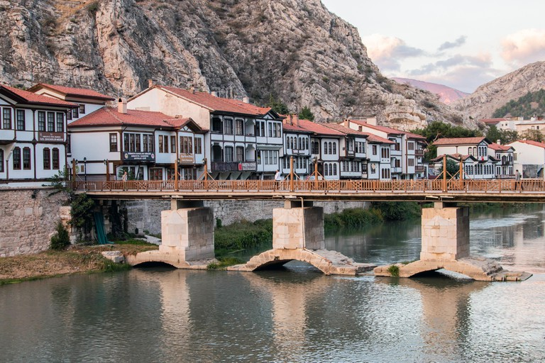Amasya, Turkey - December 7, 2019 : Old Ottoman houses and clock tower view by the Yesilirmak River in Amasya City. Amasya is populer tourist destinat