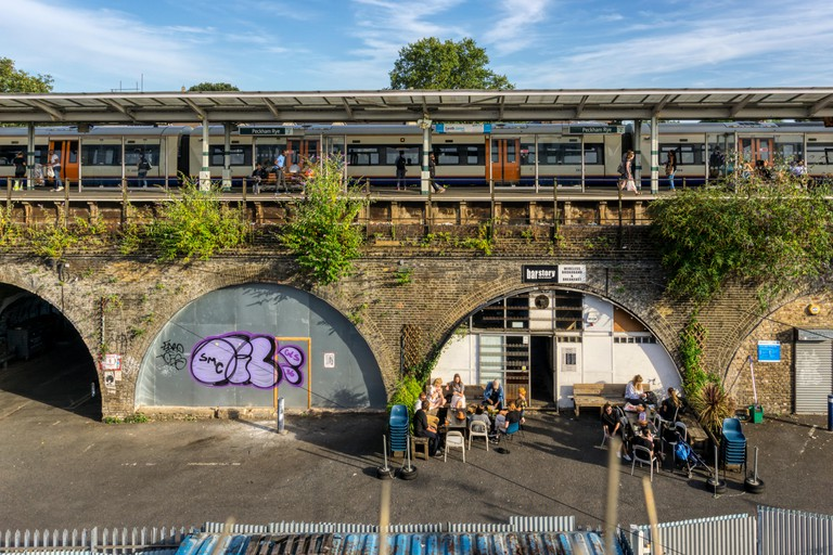 People sitting outside the Bar Story bar in a railway arch beneath Peckham Rye railway station.
