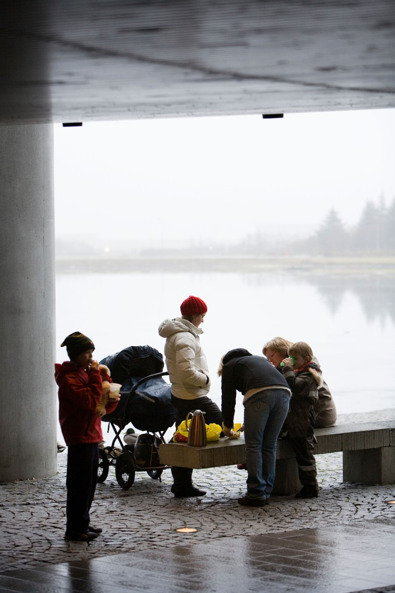 A family enjoying a picnic outside during a rainy foggy day at Reykjavik City Hall