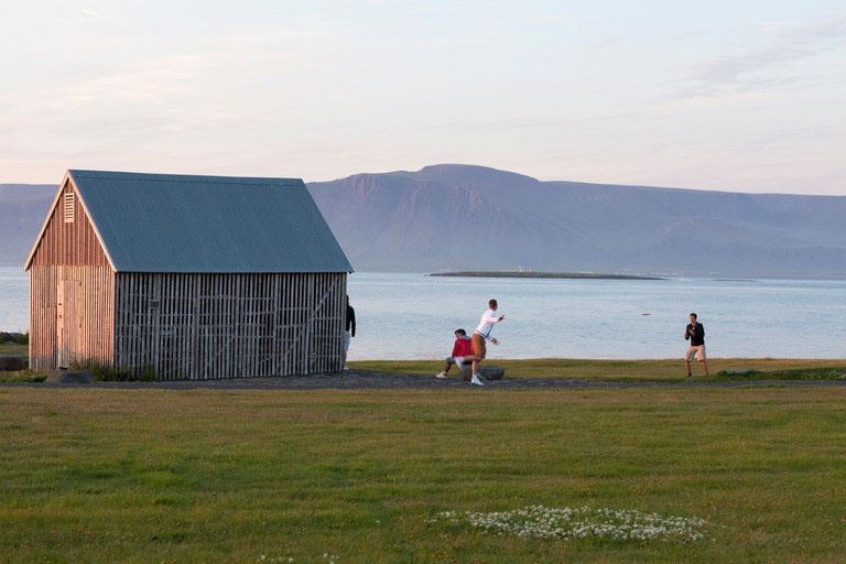 Young boys playing at midnight, at sunset in Iceland