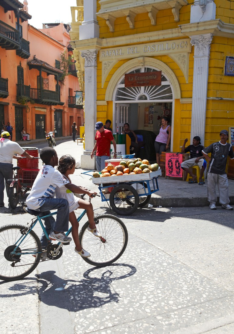 Kids riding bike through busy Cartagena street, Colombia.