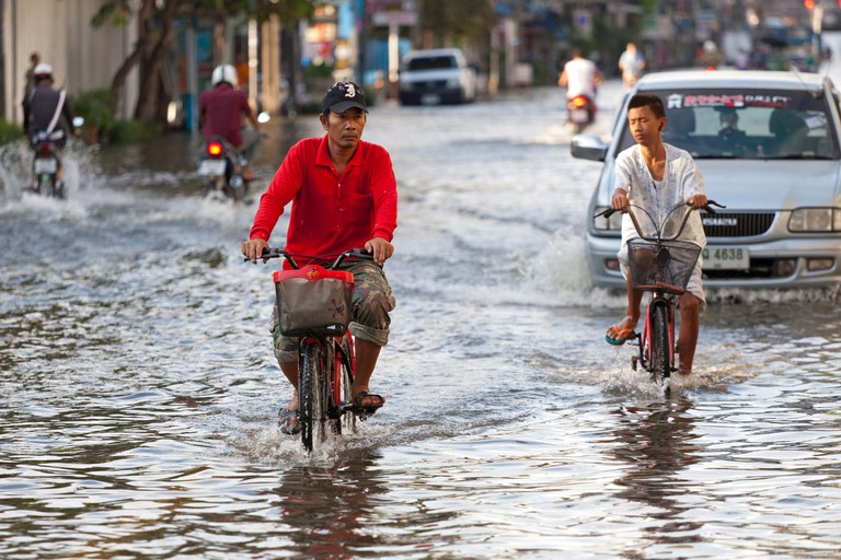 Cyclist riding through flood water in Bangkok city centre, Thailand