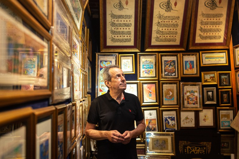 Zekai Dönerkan in his shop, Galeri Sufi, in Istanbul's Grand Bazaar, Turkey. Zekai sells a range of old Ottoman drawings, paintings, texts, and more modern pieces.