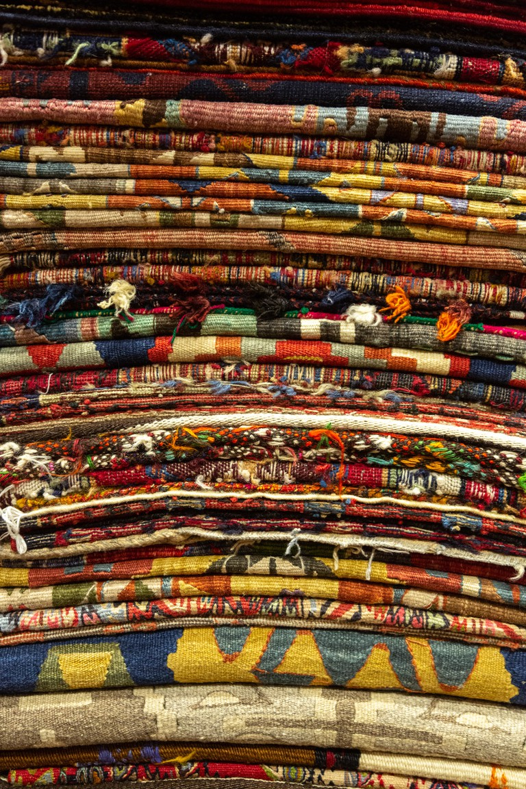 Stacks of colourful carpets and kilims at Adnan and Hasan Anatolian carpet and kilim store in the heart of Istanbul's grand bazaar.