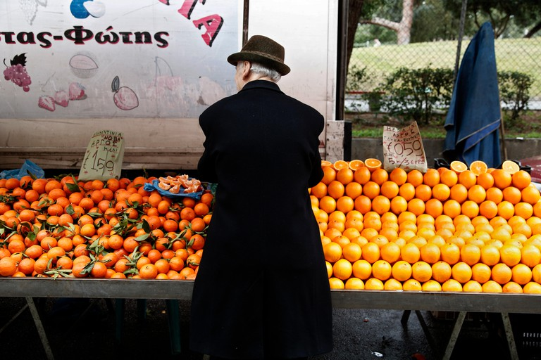 Man buys citrus at a farmers market in Thessaloniki