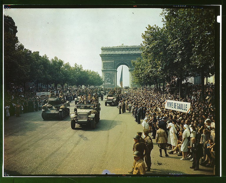 Crowds of French patriots line the Champs Elysees to view Allied tanks and half tracks pass through the Arc du Triomphe, after Paris was liberated on August 25, 1944.