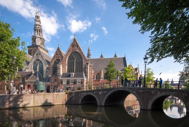 Amsterdam De Oude Kerk, The Old Church with Oudekerksbrug (Old Church Bridge) and Oudezijds Voorburgwal Canal.
