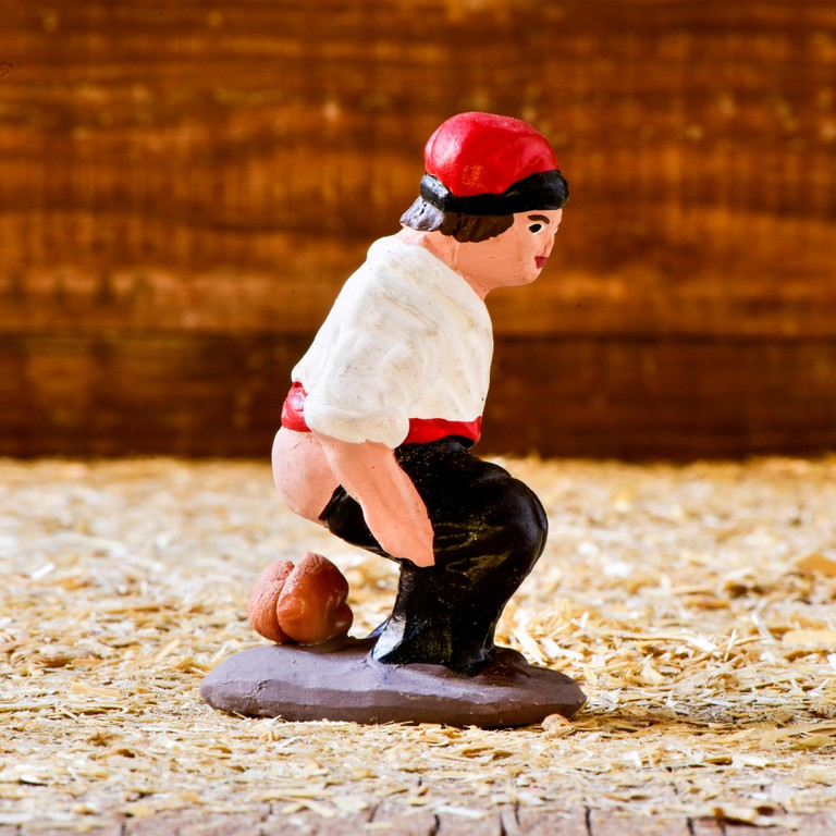 closeup of the caganer, a typical catalan character in the nativity scenes of Catalonia, Spain depicting a catalan peasant defec