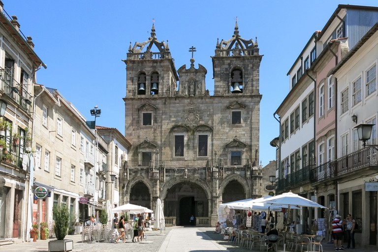Street scene with people, pavement cafe, souvenir shop and Cathedral Santa Maria in old town of Braga, Portugal