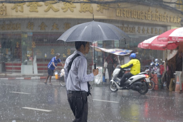 Residents make their way to work during a recent thunderstorm in Bangkok.