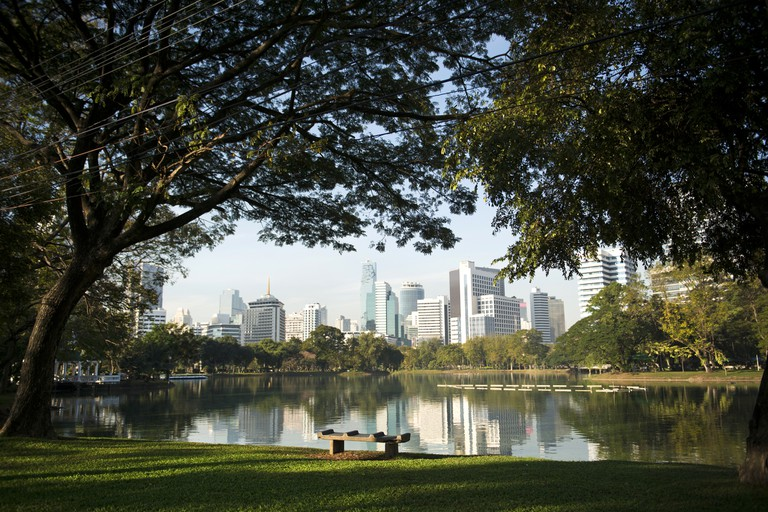 A bench inside Lumphini park covered by large trees with the view of Bangkok skyscrapers over the
