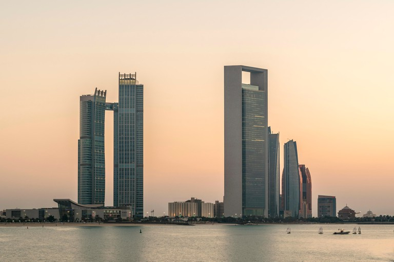 Abu Dhabi Corniche sunset.  Dusk over the coastline and the corniche with Etihad Towers on the skyline