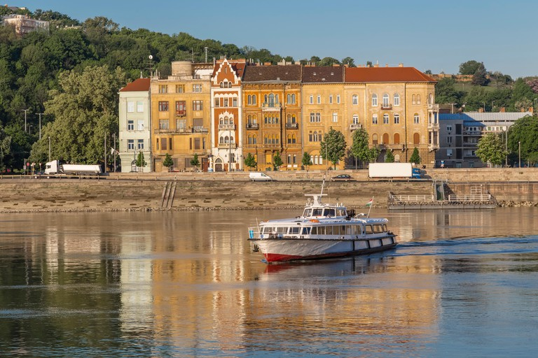 Boat sails across the river on the background of old houses. Budapest. Hungary