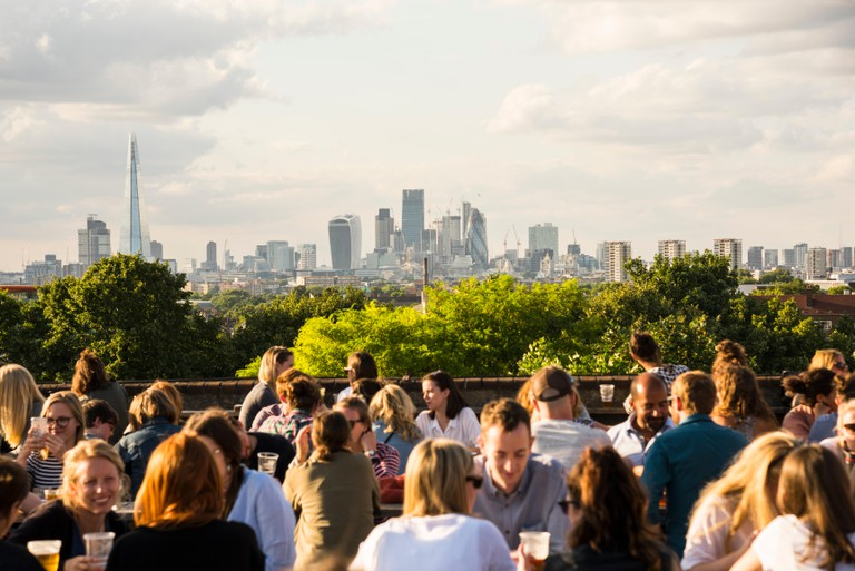 Young people socialising, enjoying a drink together at Franks Cafe outdoor rooftop bar and restaurant in Peckham, South London with view of the city.