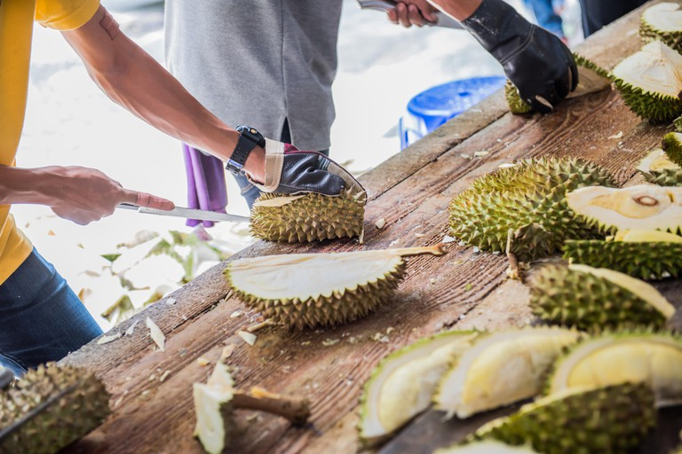 peeling durian by knife. Thai King fruit