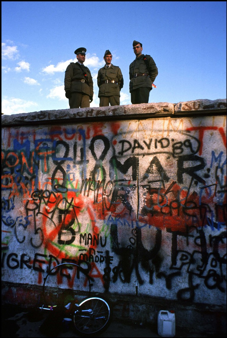 East German border guards standing atop the Berlin Wall look to the West. Berlin, Germany.