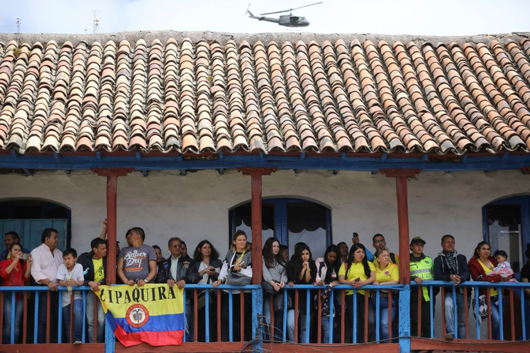 Locals look from a balcony as Tour de France winner Egan Bernal arrives to Zipaquira, Colombia.