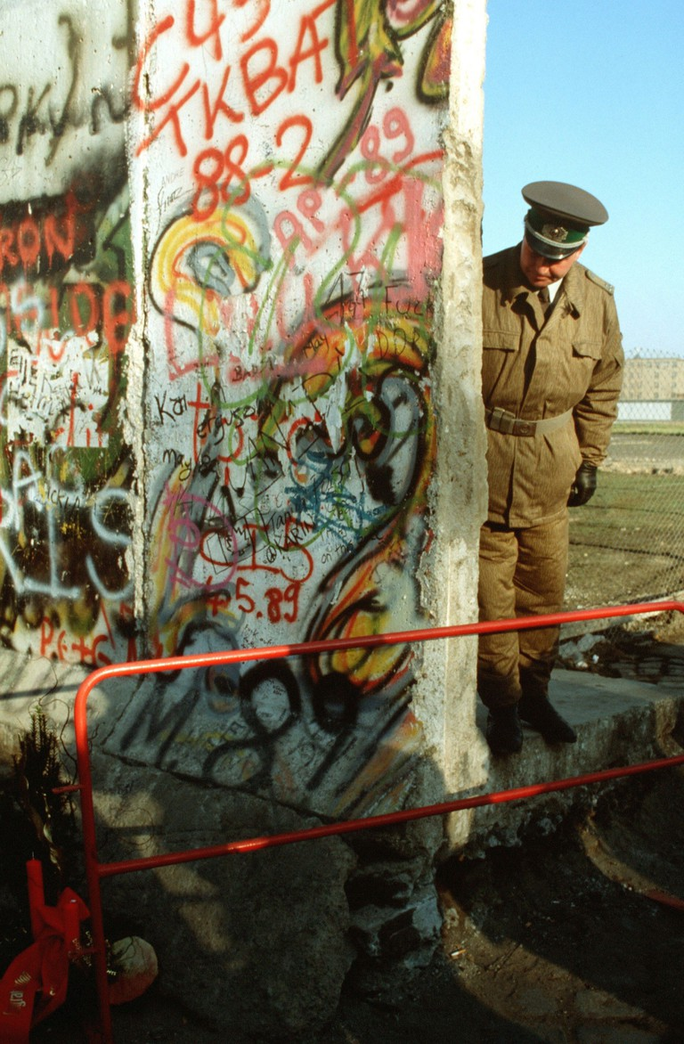 An East German policeman looks at a small Christmas tree adorning the West German side of the Berlin Wall. 14 November 1989