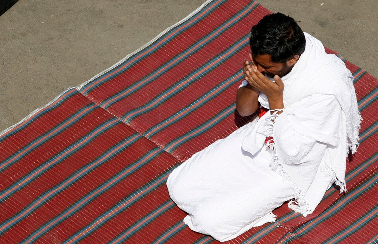 A Muslim pilgrim praying the noon prayer in Mina near Mecca, Saudi Arabia.