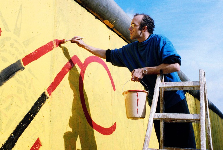 New York artist Keith Haring decorates the Berlin Wall with 100 meters of graffiti. The artist, begins his work near West Berlin's Checkpoint Charlie
