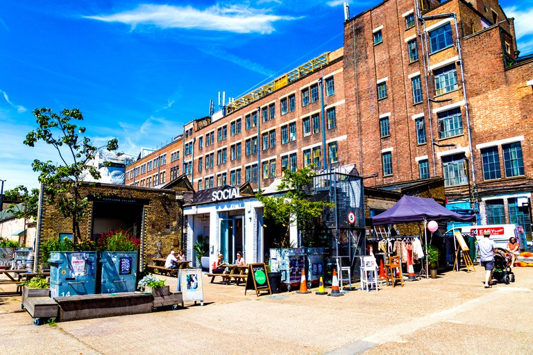 Social cafe, bar and restaurant with the Bussey Building in the background, in Copeland Road Park, Peckham, London, UK