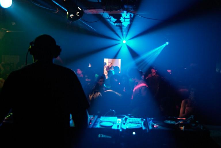 DJ Playing a Set in a Crowded Nightclub