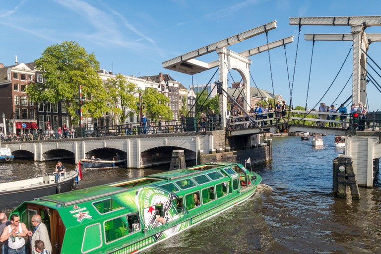 Amsterdam Heineken shuttle canal cruise boat with Magere Brug, Skinny Bridge, on the Amstel River canal with small boats