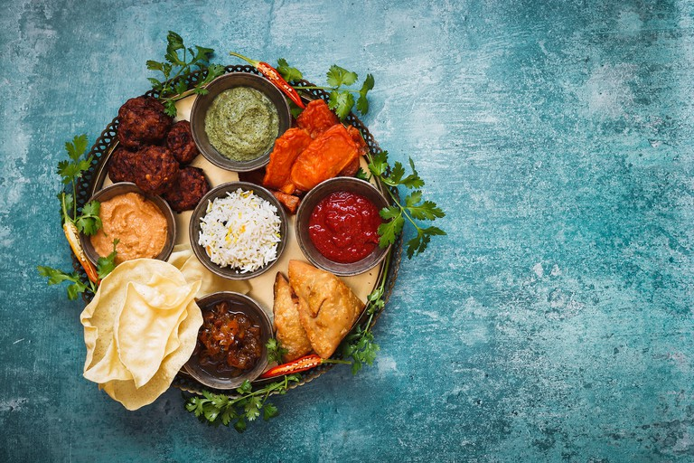 Vegetarian Thali. Indian appetizers and snacks: pakora, samosas and bhaji served with chutneys and other dipping sauces  on rustic surface