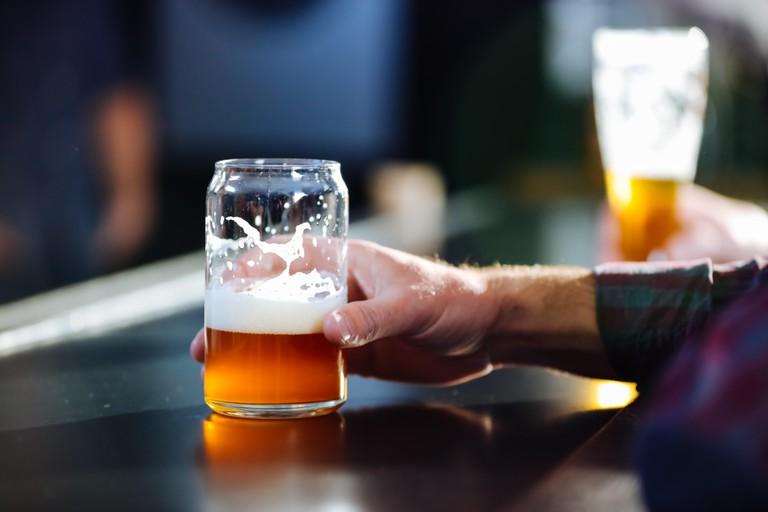 A Man Enjoying A Craft Beer At A Brew Pub
