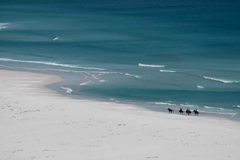 Horse riders taking a stroll on beach at Noordhoek