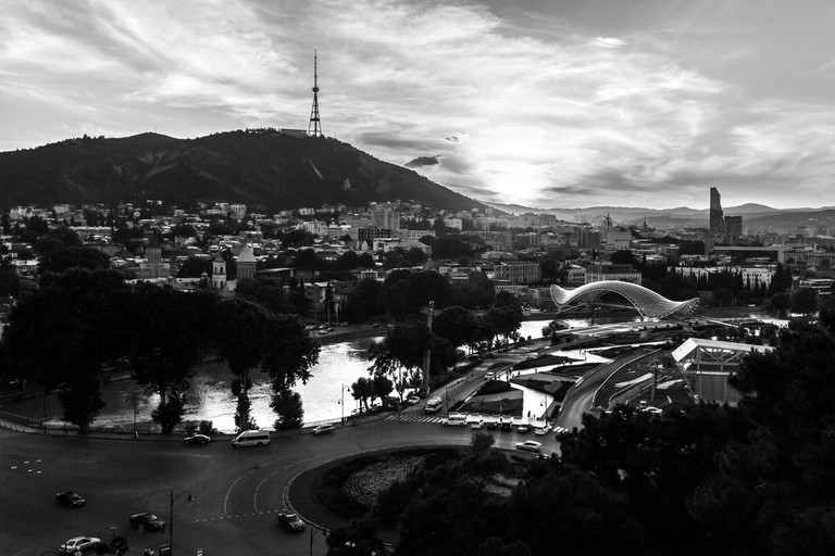 Black and white view of glass Bridge of Peace in old Tbilisi at sunset, Georgia, Europe