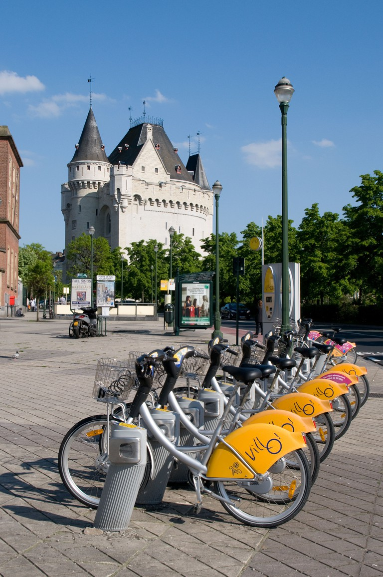 A line of bicycles for hire at Porte De Hal (Halleport) wait for customers. The medieval fortified gate stands in the background