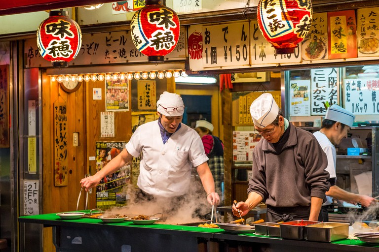 Japanese chefs prepare takoyaki and other snack foods at a stall in Osaka, Japan.