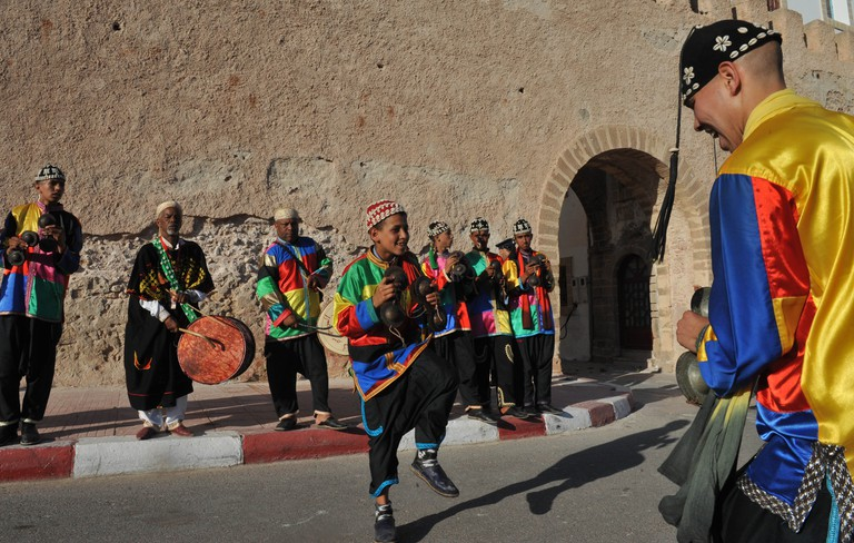 Members of a Gnaoua troupe parade along a street in Essaouira during the Gnaoua World Music Festival