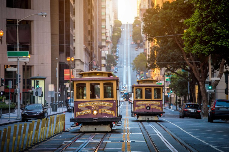 Classic view of historic traditional Cable Cars riding on famous California Street in beautiful morning light at sunrise in summer, San Francisco, USA